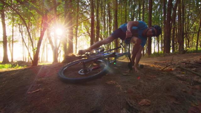 low angle shot of mountain biker coming around corner and falling off his bike - タートル湾点の映像素材/bロール