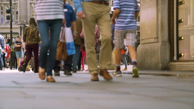 low angle shot of pedestrians walking along a pavement near oxford circus, london. - pavement stock-videos und b-roll-filmmaterial
