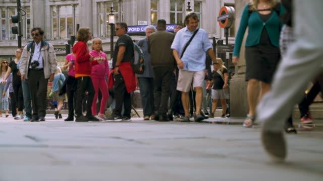 Low angle shot of pedestrians walking along Oxford Street, London.