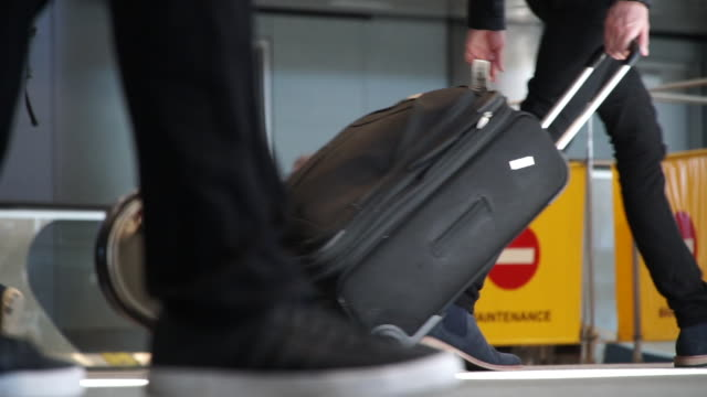 vidéos et rushes de low angle shot of people maneuvering through denver airport with their luggage 2019 - bagage