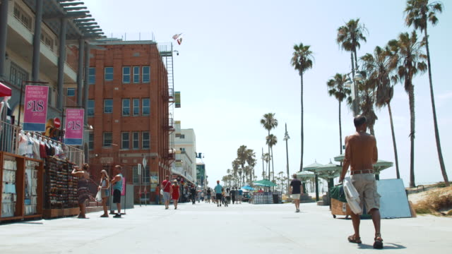 Low angle shot of people walking along the Venice Beach Boardwalk in Los Angeles California