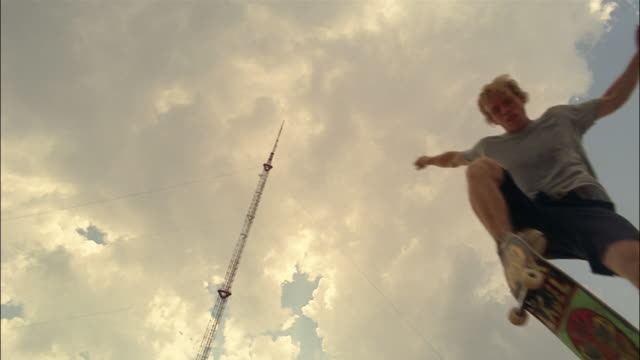 low angle shot of pole against clouds in sky / slow motion of skater performing ollie over camera - stunt stock videos & royalty-free footage