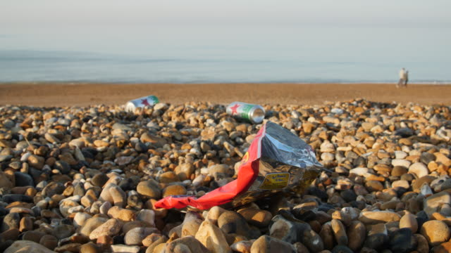 low angle shot of rubbish strewn across brighton beach - brighton brighton and hove stock-videos und b-roll-filmmaterial