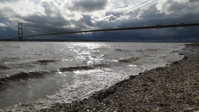 low angle shot of sea lapping shoreline with hull skyline and humber bridge in background - overcast stock videos & royalty-free footage
