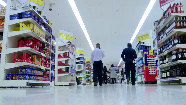 Low angle shot of shoppers browsing the aisles of a Tesco supermarket