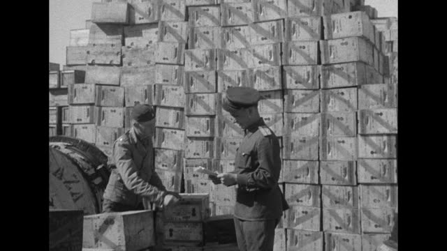 vidéos et rushes de ms low angle shot of tank / mstilt down crates stacked high soviet soldiers take inventory / mspan high angle of military trucks sitting in yard - forces alliées