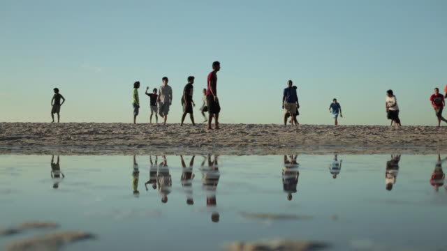 low angle shot of teenagers playing football on camp bay beach, cape town. - 澄んだ空点の映像素材/bロール