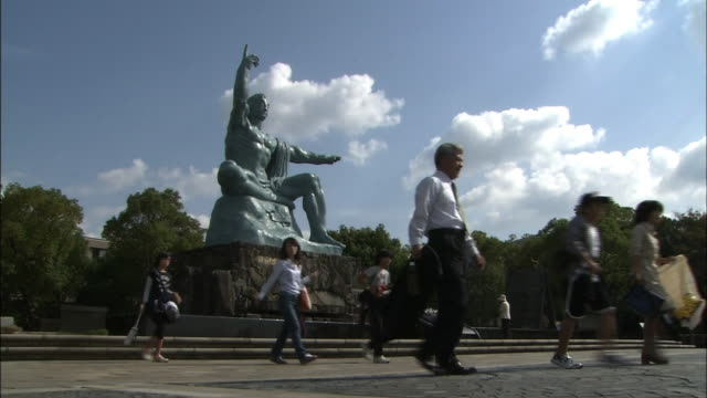 low angle shot of the peace statue in nagasaki peace park. people walking around the statue. - massenvernichtungswaffe stock-videos und b-roll-filmmaterial