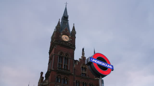 Low angle shot of the St Pancras Hotel with a London Underground sign in the foreground.