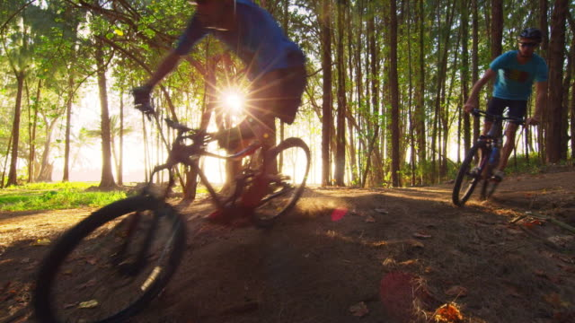 low angle shot of two mountain bikers racing around a corner - turtle bay hawaii stock videos & royalty-free footage