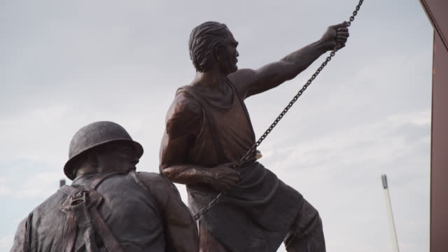 Low angle shot of two muscular American iron-workers, from the tribute to labor sculpture along the Missouri River, titled 'Labor' by Matthew Placeck.
