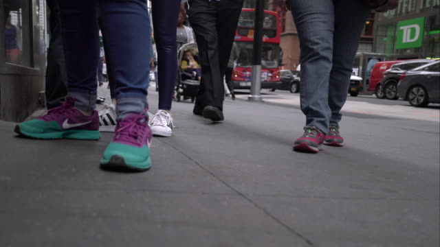 Low angle shot of various New York City pedestrians on the sidewalk moving in and out of frame.