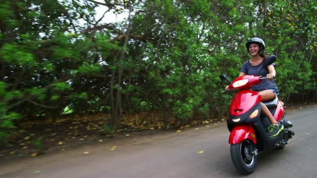 low angle shot of woman laughing while riding moped - ehefrau stock-videos und b-roll-filmmaterial