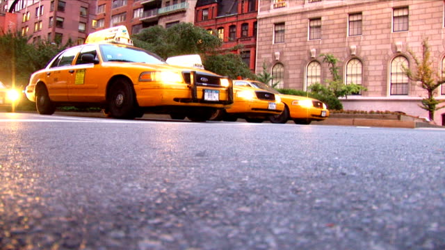 low angle shot of yellow cabs on an american city street. - yellow taxi stock videos & royalty-free footage