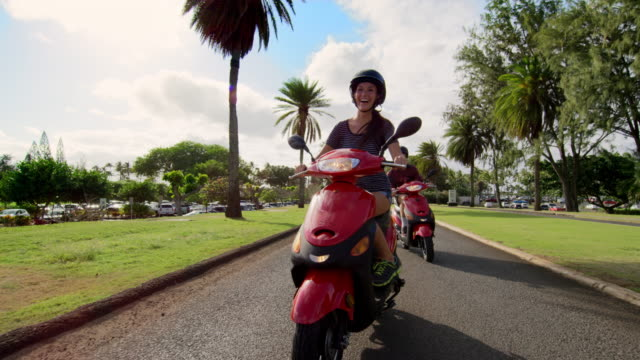 Low angle shot of young couple riding mopeds togther along palm grove