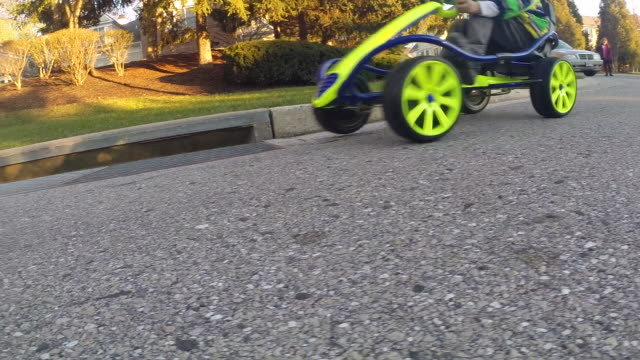 low angle shot on go-cart wheels drive by with boy driving on  residential road. - kelly mason videos stock videos & royalty-free footage