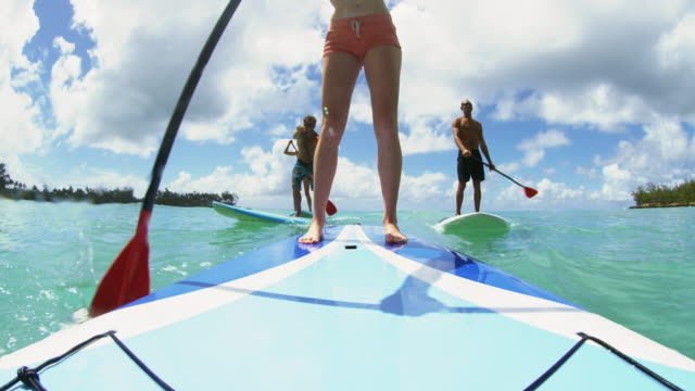 vídeos de stock, filmes e b-roll de low angle shot on nose of a paddle board facing paddle boarders - 50 anos