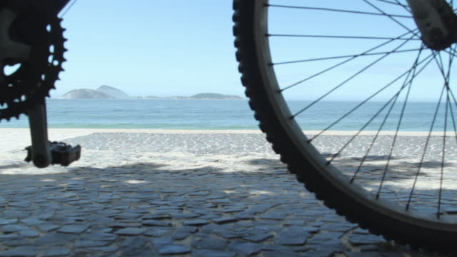 low angle shot panning across the front wheel of bicycle, parked on rio's seafront. - surface level stock videos & royalty-free footage