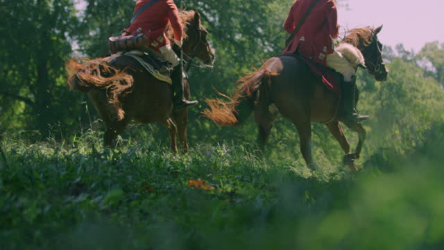 low angle shot of two horsemen galloping away in a meadow - bridle stock videos & royalty-free footage