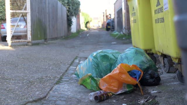 low angle shot showing a pile of plastic bags and other items that have been left in the streets of northampton. - northampton stock-videos und b-roll-filmmaterial
