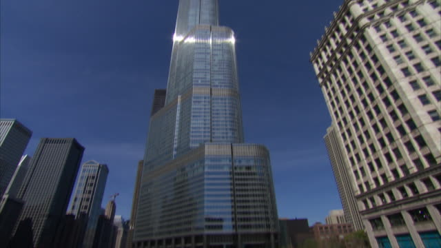 low angle shot trump and wrigley buildings pan left and tilt down to chicago river - レガッタリグレービル点の映像素材/bロール