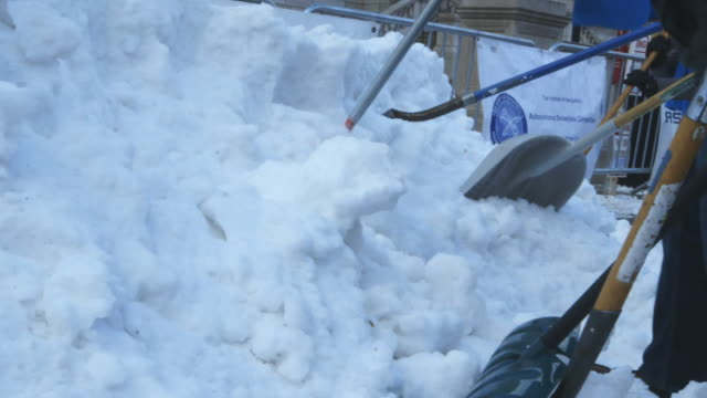 Low angle, shoveling snow