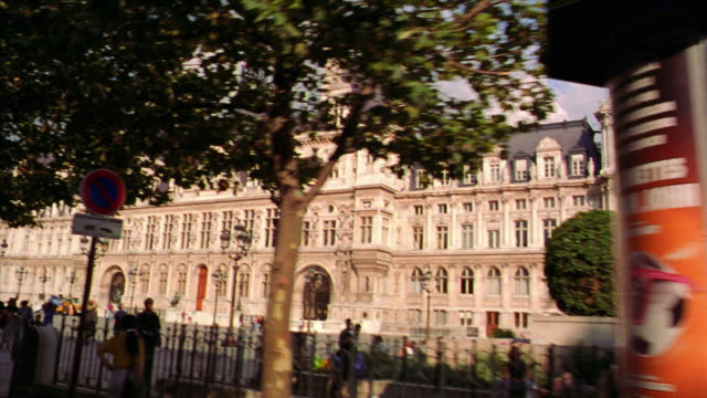 low angle side car point of view PAN Hotel de Ville with trees + people on sidewalk in foreground / Paris, France