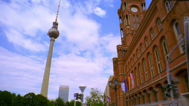 low angle side car point of view past Berlin Town Hall (Berliner Rathaus) + Television Tower with park in foreground / Berlin