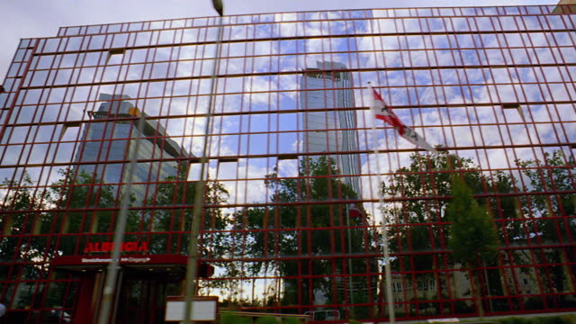 low angle side car point of view past mirrored building on city street / frankfurt, germany - autoperspektive stock-videos und b-roll-filmmaterial