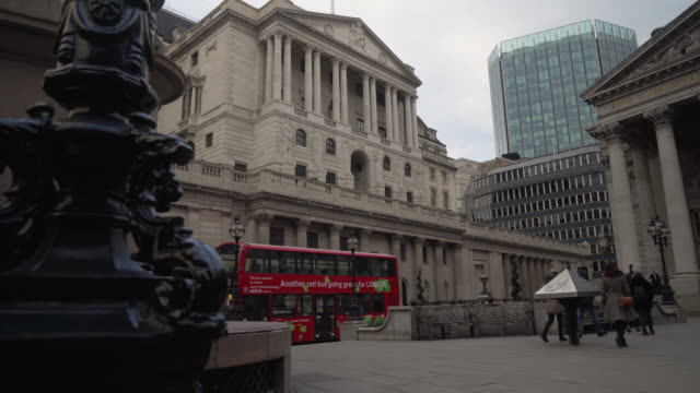 Low angle side tracking shot across the exterior of the Bank of England building on Threadneedle Street, London.