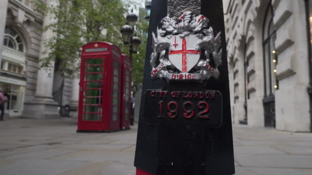low angle side tracking shot from a lamppost to red telephone boxes on a pedestrianized street in the city of london. - telefonzelle stock-videos und b-roll-filmmaterial