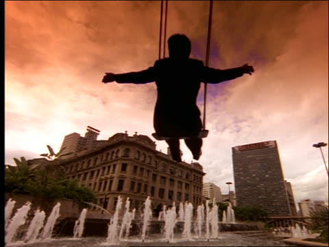 low angle sil of businessman on swing / fountain + city in background / brazil - one mid adult man only stock videos & royalty-free footage