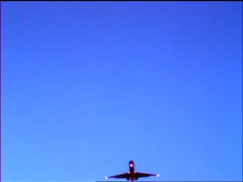 stockvideo's en b-roll-footage met low angle silhouette airplane flying overhead in blue sky - 1990