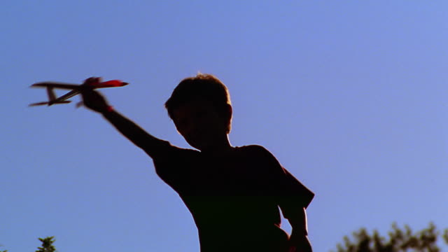 canted low angle ms silhouette boy spinning in circles holding toy airplane above head outdoors - model aeroplane stock videos & royalty-free footage