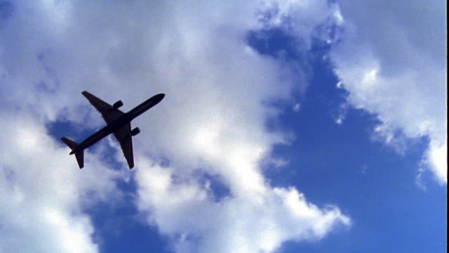 low angle PAN silhouette of airliner ascending directly overhead in blue sky with white clouds