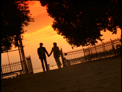 canted low angle silhouette of couple holding hands skipping + running at sunset / fence in background / venice - skipping stock videos & royalty-free footage