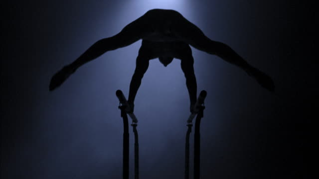 stockvideo's en b-roll-footage met low angle silhouette of male gymnast performing routine on parallel bars - de brug