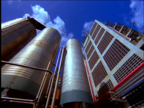 low angle PAN of silos (storage tanks) at oil refinery / Brazil