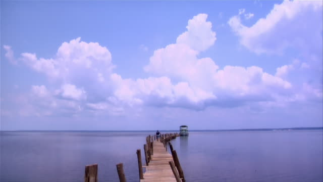 Low angle sky/ tilt down wide shot person walking on pier out to ferry in Rio Negro/ The Amazon, Brazil