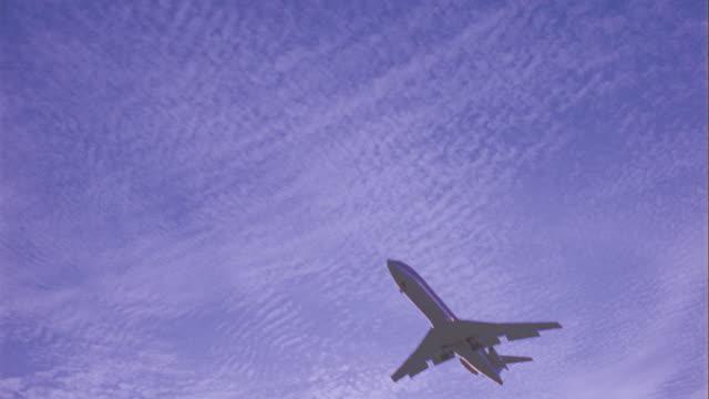 low angle slight pan airliner flying over camera / clouds in background - mindre än 10 sekunder bildbanksvideor och videomaterial från bakom kulisserna