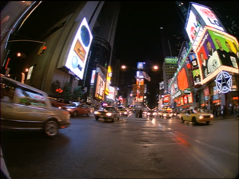 low angle slight fisheye traffic going past camera in times square at night / new york city - 1998 stock-videos und b-roll-filmmaterial