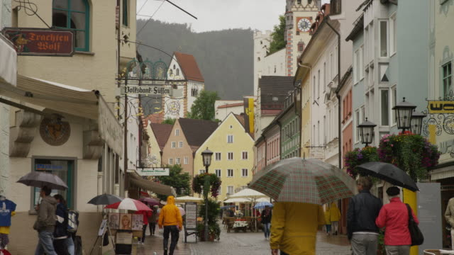 Low angle slow motion panning shot of crowd walking on city street in rain / Fussen, Bavaria, Germany