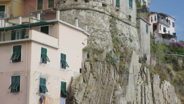 Low angle slow motion panning shot of houses built on rocky hillside / Vernazza, Cinque Terre, Italy