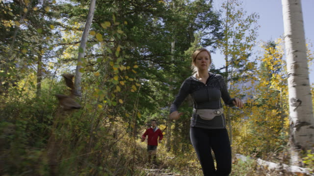 Low angle slow motion tracking shot of runners on remote trail / American Fork Canyon, Utah, United States