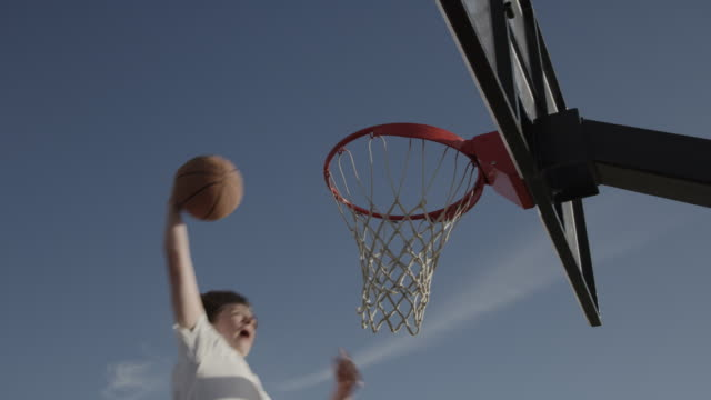 low angle slow motion view of boy dunking basketball / lehi, utah, united states - lehi stock videos & royalty-free footage