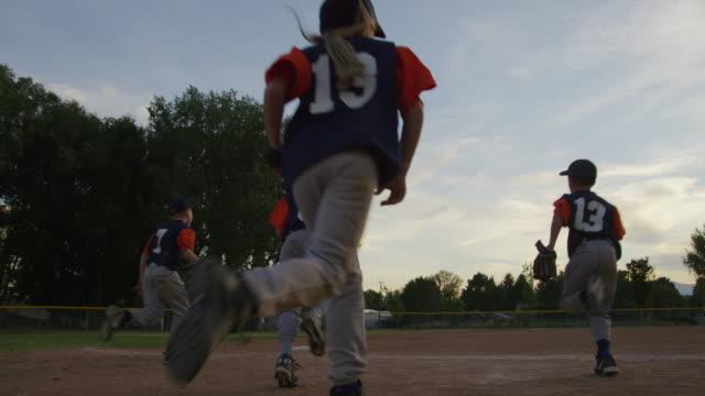 low angle slow motion wide shot of baseball team running onto field / american fork, utah, united states - baseballmannschaft stock-videos und b-roll-filmmaterial