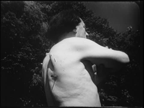 b/w 1951 low angle small darts flying into back of shirtless man / newsreel - shirtless stock videos & royalty-free footage