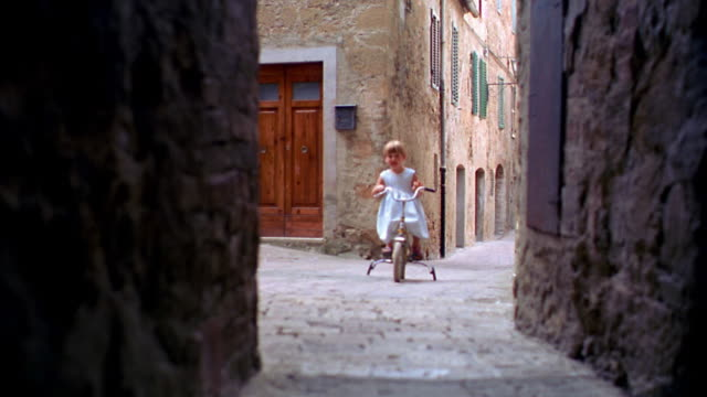 low angle small girl riding bicycle with training wheels towards camera in alley / pienza, italy - toscana video stock e b–roll