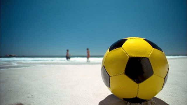 vídeos y material grabado en eventos de stock de low angle soccer ball on beach in foreground / man running toward cam and kicking ball / frisbee players in background - pelota