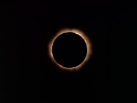 low angle solar eclipse at totality with solar corona around umbra